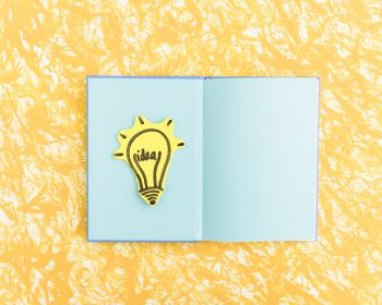 Idea Light Bulb On Blue Page Notebook Over The Yellow Textured Background