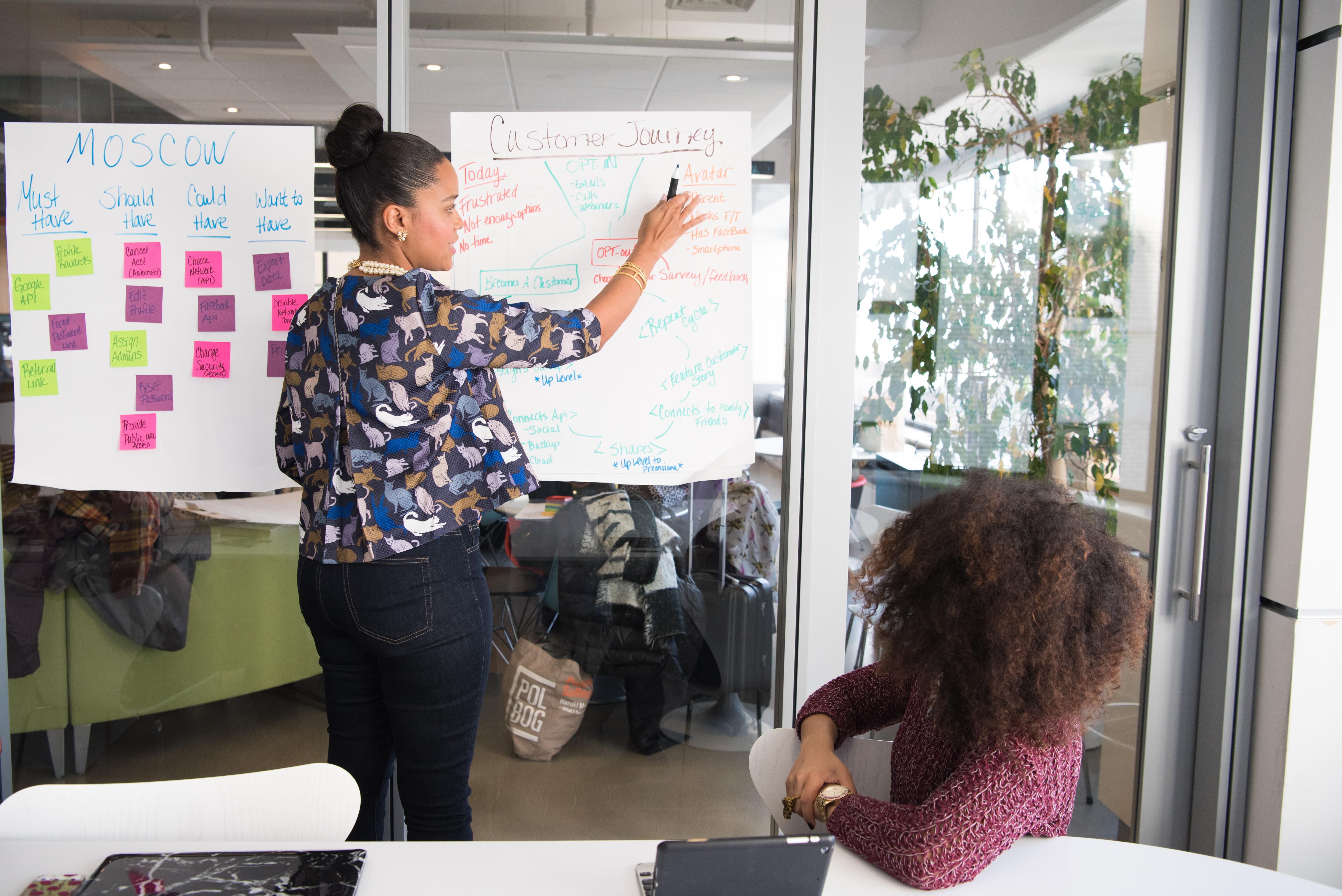Two Women Having A Meeting Inside Glass Panel Office 1181615