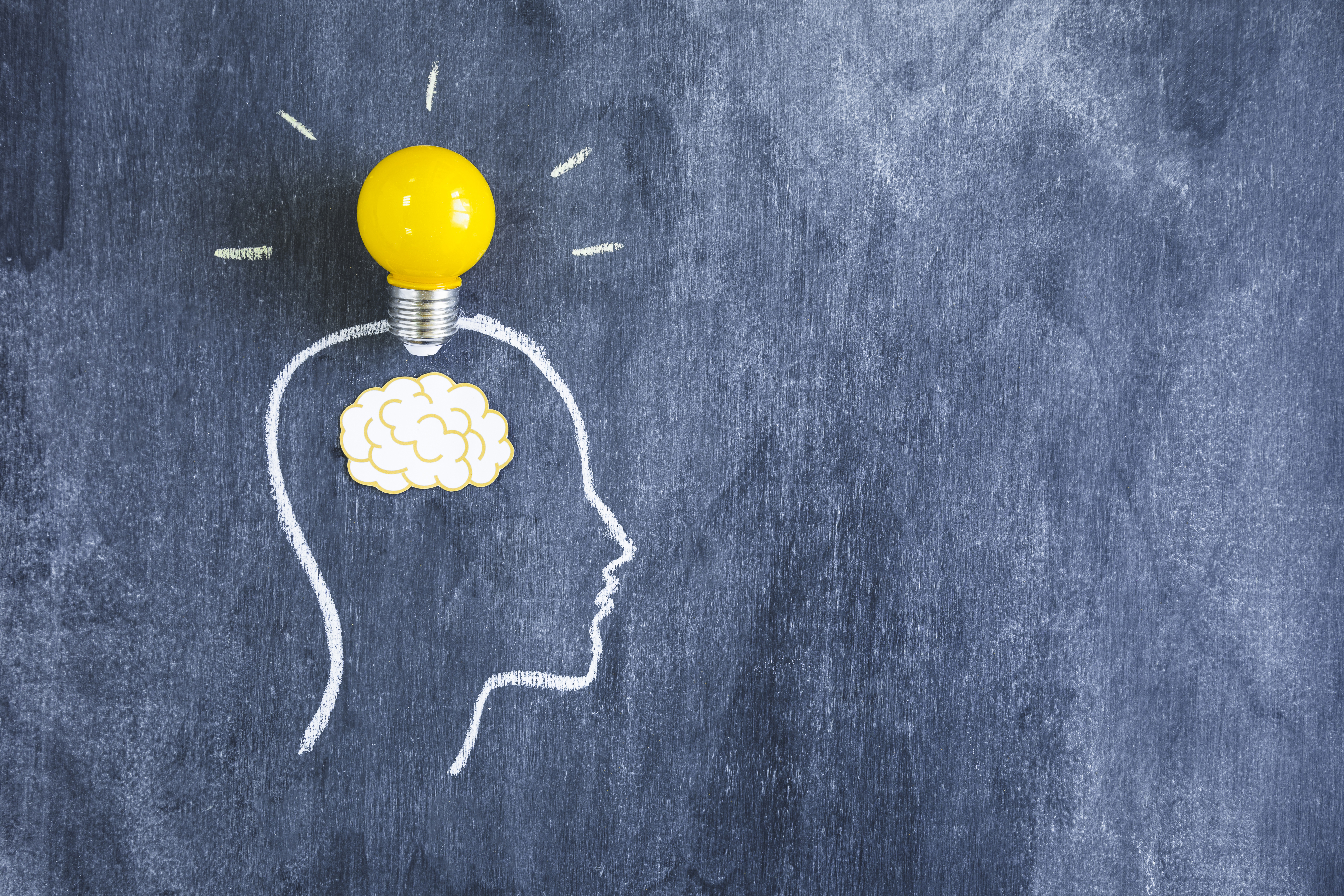Yellow Light Bulb Over The Paper Cutout Brain On The Outline Face Made With Chalk Over The Blackboard