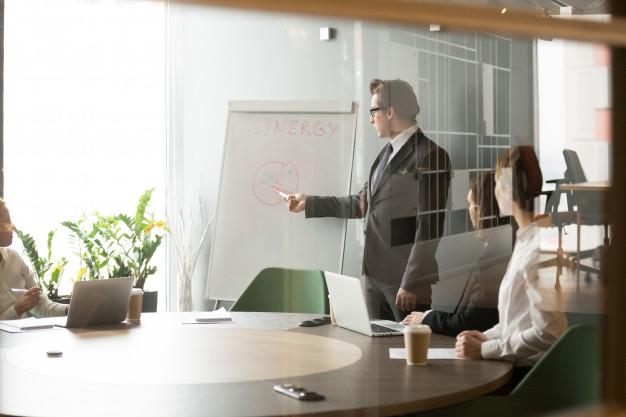Homem De Negocios Serio Apresentando Objetivos De Negocio Da Empresa Para Os Colegas 1163 4781